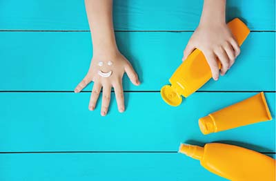 childs hands with bottles of sunscreen