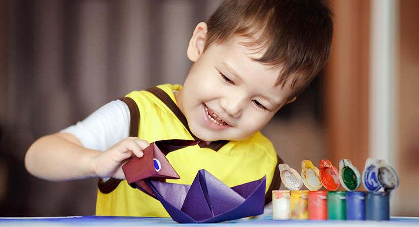 Young boy playing with paper boat