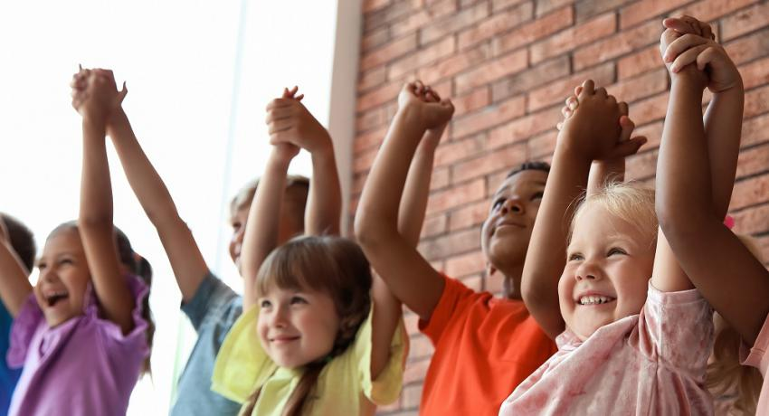 Kids raise their arms and lock hands while smiling.